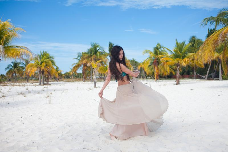 Girl travels to sea and is happy. Young attractive brunette woman dancing waving her skirt against tropical landscape royalty free stock photography