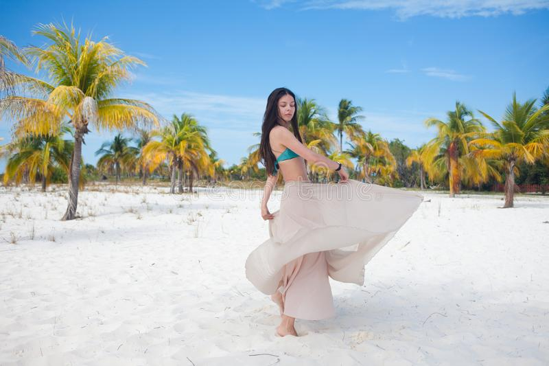 Girl travels to sea and is happy. Young attractive brunette woman dancing waving her skirt against tropical landscape royalty free stock images
