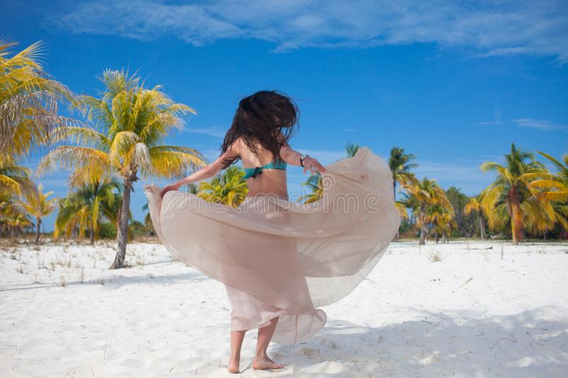 Girl travels to sea and is happy. Young attractive brunette woman dancing waving her skirt against tropical landscape royalty free stock photos