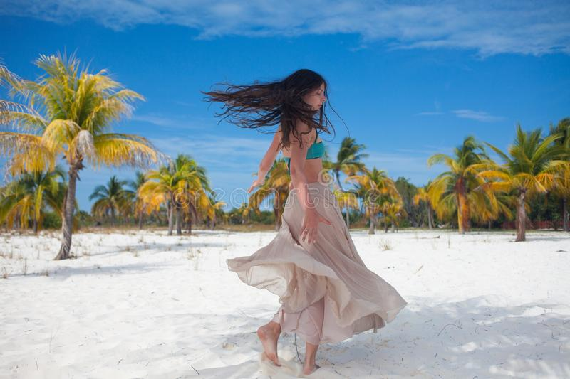 Girl travels to sea and is happy. Young attractive brunette woman dancing waving her skirt against tropical landscape stock images