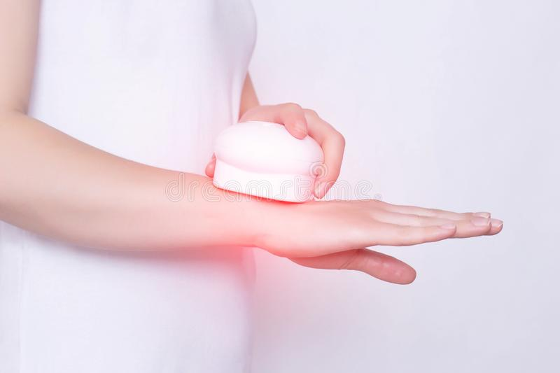 Girl treats a sore wrist joint with the help of physiotherapy and magnet laser treatment, white background, damage. Girl treats a sore wrist joint with the help stock photo