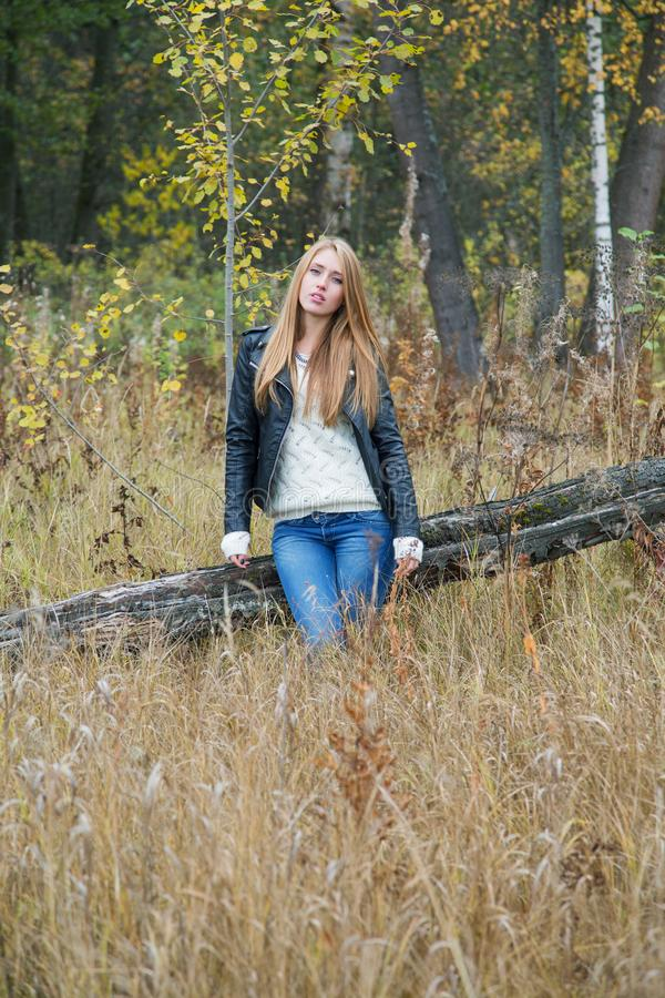 Girl among the trees in the high yellow grass stock image