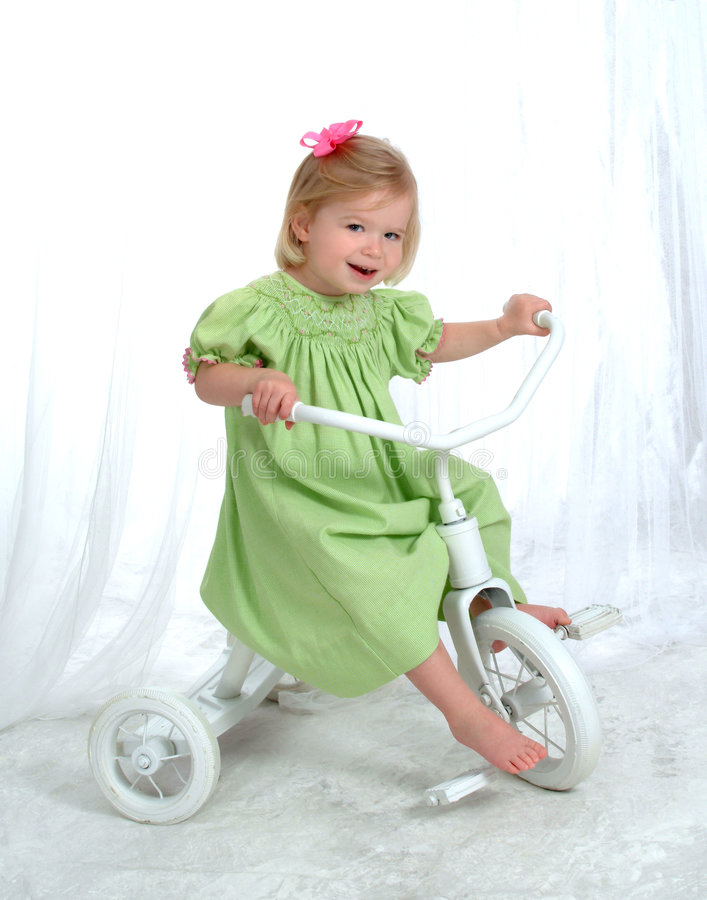 Girl on Tricycle. Girl in green on tricycle in front of white background stock photography