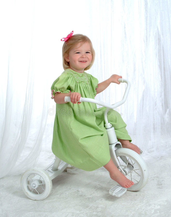 Girl on Tricycle. Girl in green on tricycle in front of white background stock image