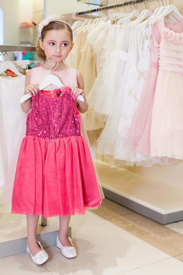 Girl tries on a bright red dress in the modern store royalty free stock images