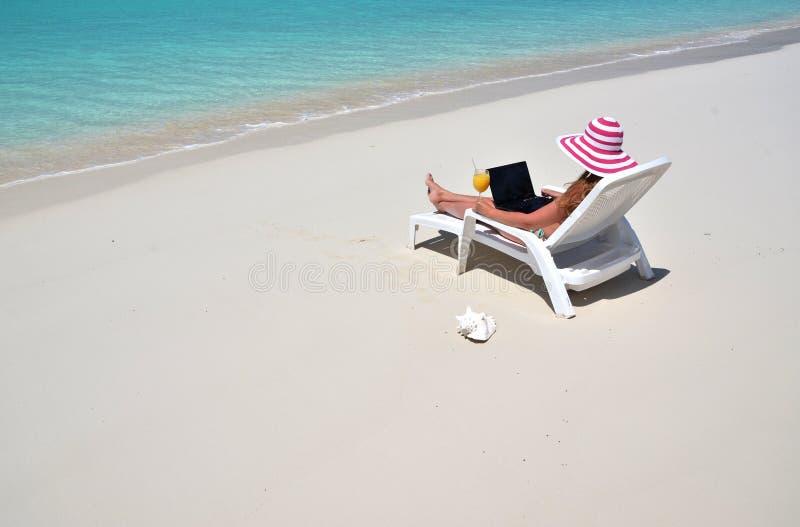 Girl on the tropical beach. Exuma, Bahamas. Girl with a laptop on the tropical beach. Exuma, Bahamas royalty free stock images