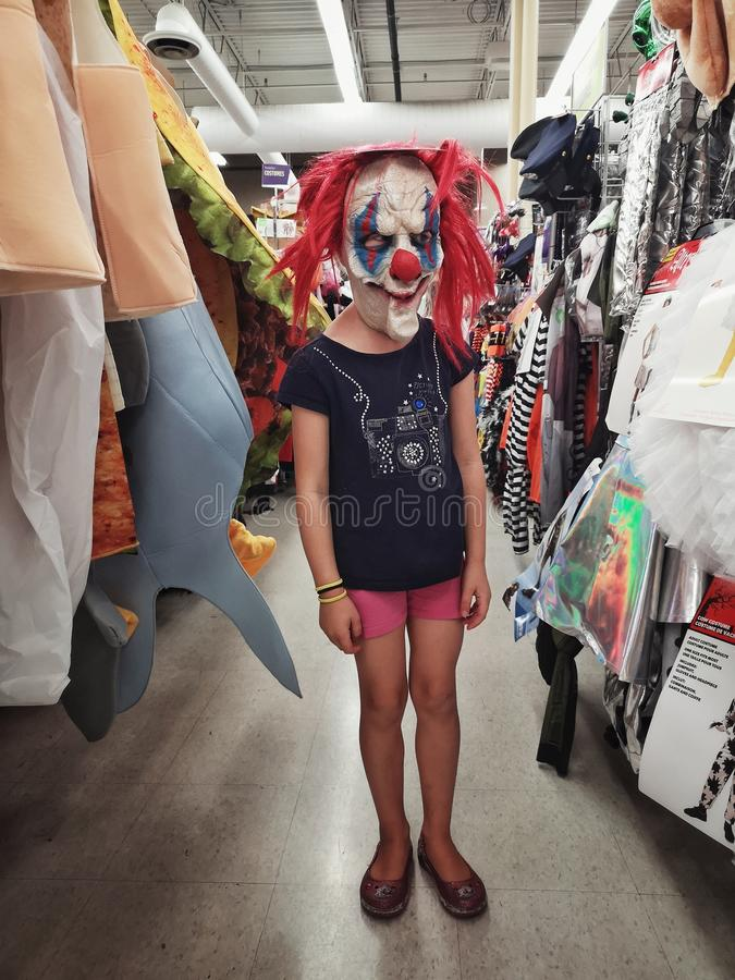 Girl trying on costume spooky scary creepy clown mask in store for Halloween holiday celebration stock images