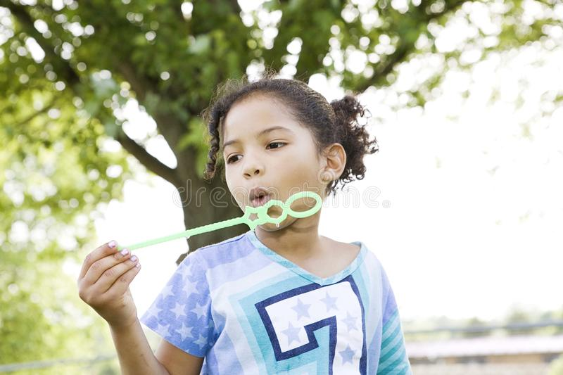Girl trying to blow bubbles royalty free stock images