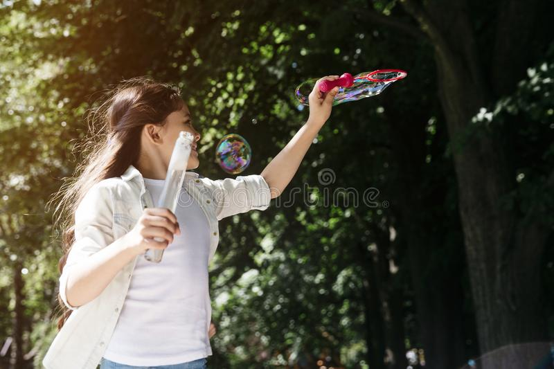 Girl is trying to blow soap bubbles using wind for that. She is waving with the tool that makes soap bubbles. Girl is. Looking up royalty free stock photo