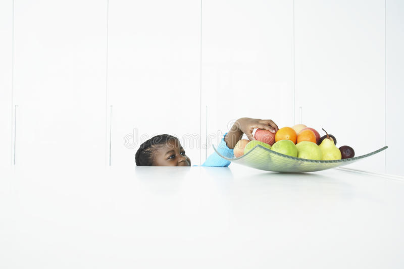 Girl Trying To Reach Fruits In Dish stock photos