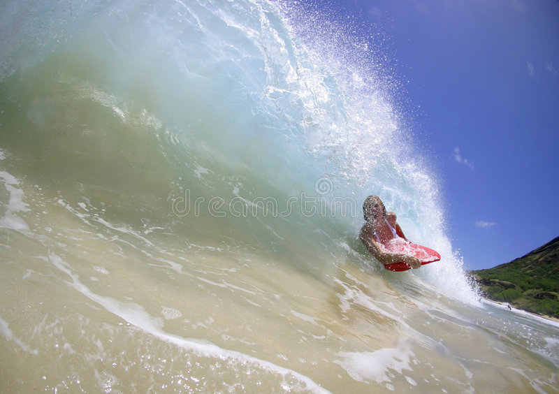Girl in the Tube of a Surfing Wave stock photos