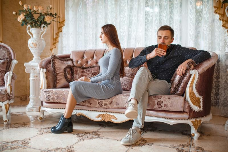 The girl turned away from the guy sitting on the couch at a reception with a psychologist stock photo