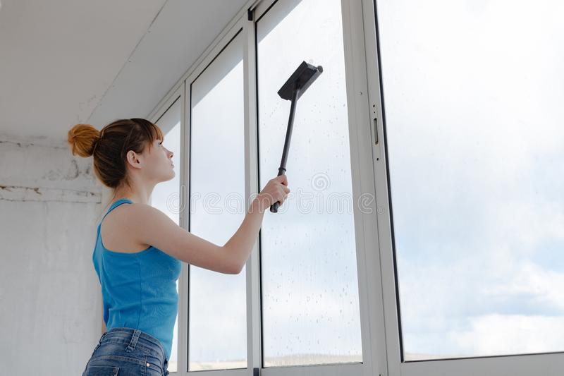 The girl in the turquoise T-shirt and blue shorts washes the window royalty free stock image