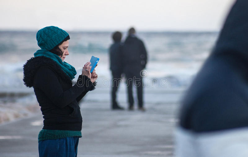 Girl on turquoise typing on the phone royalty free stock photo