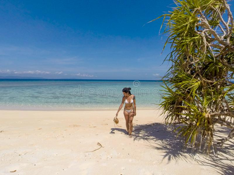 Girl on turquoise water and white beach in Camiaran island in Balabac in Philippines royalty free stock photo