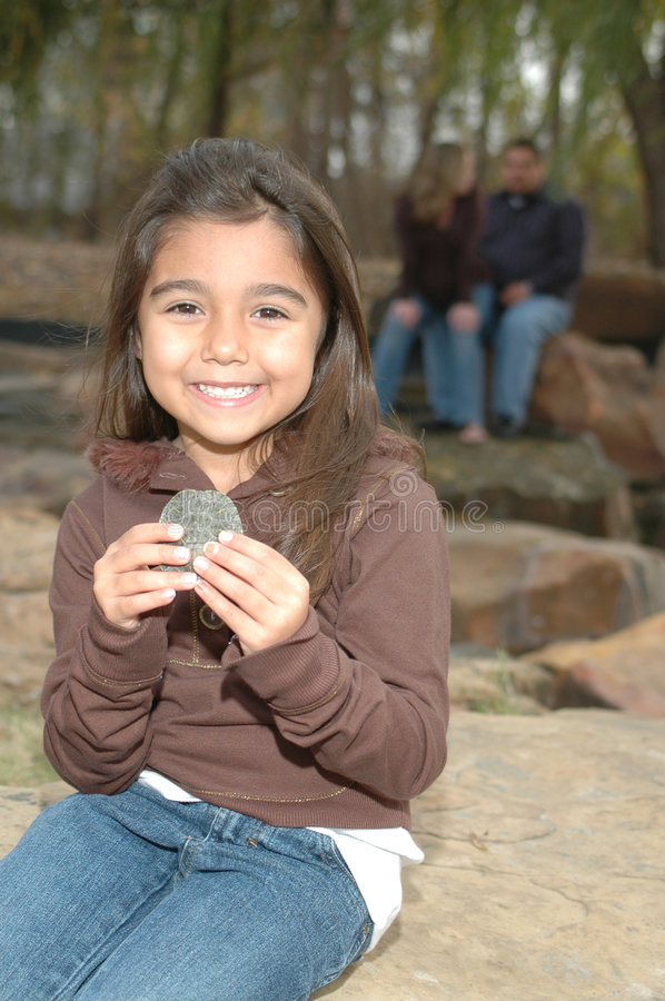 Girl with a Turtle. Happy little girl sitting on a rock holding a small turtle while her parents sit behind her stock photo