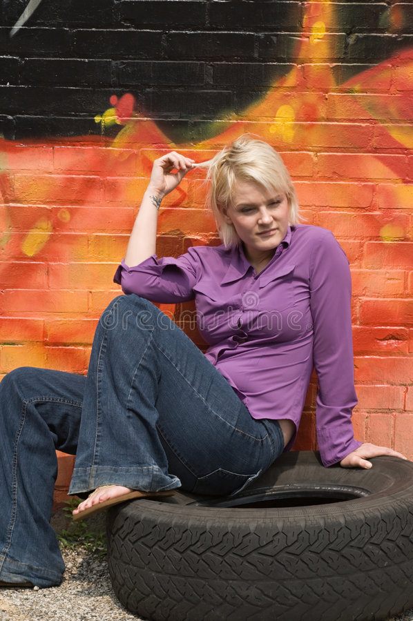 Girl Twisting Hair. Blond woman sitting on old tire and twisting her hair royalty free stock photo
