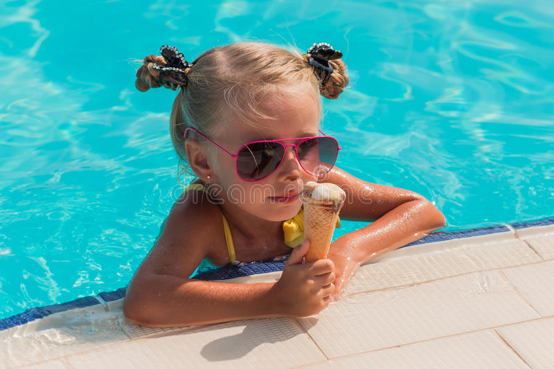 The girl with two pigtails floating in the pool on a sunny day royalty free stock photos