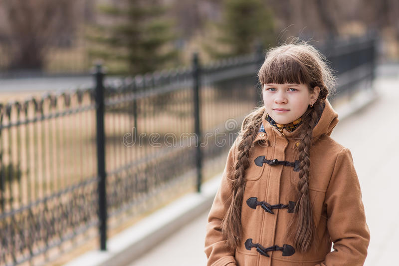 Girl with two pigtails walks in the park autumn day royalty free stock image
