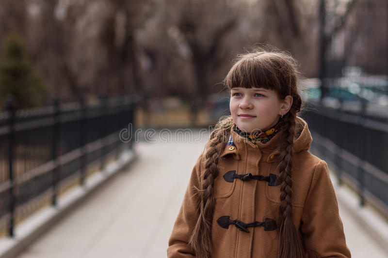 Girl with two pigtails walks in the park autumn day stock photos