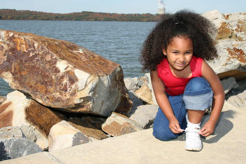 Girl tying her shoe. A young girl outside near the river stops to tie her shoe stock images