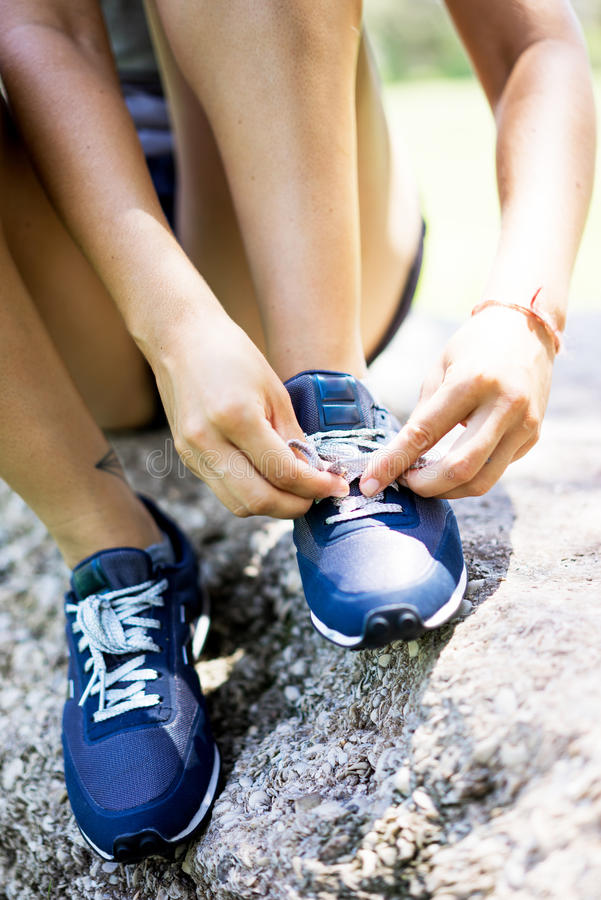 Girl tying her shoes stock image