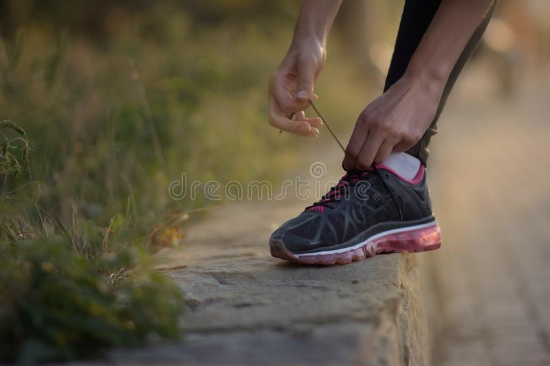 Girl tying shoelaces on running shoes for a run. On the street royalty free stock photo
