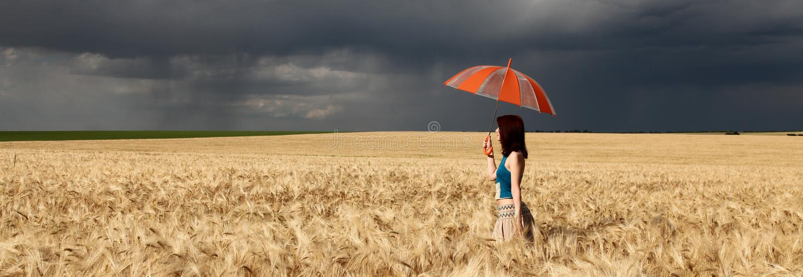 Girl with umbrella at field. in storm royalty free stock image