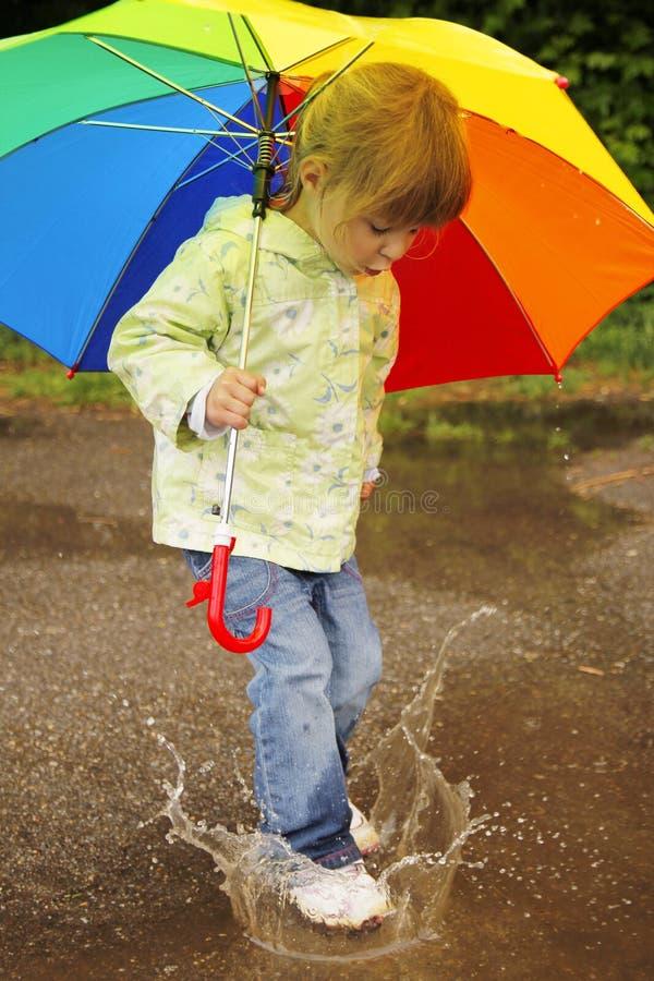 Girl with an umbrella in the rain. Little girl with an umbrella in the rain stock photos