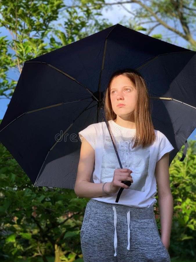 Girl with umbrella in a rainy day stock photography