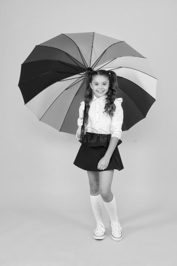 Girl with umbrella. Rainy day walks. Happy childhood. School time. Rainbow style. Colorful life. Schoolgirl happy with. Umbrella. Fall weather forecast. Fashion stock photography