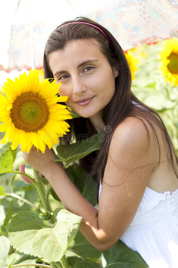 Girl with umbrella in a sunflower field stock photo