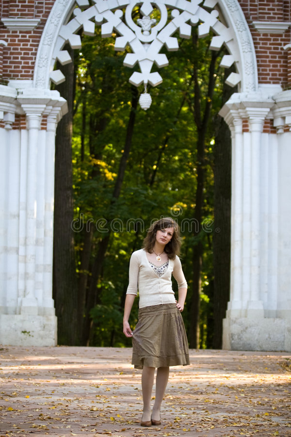 Girl under ark. In autumn park royalty free stock photo