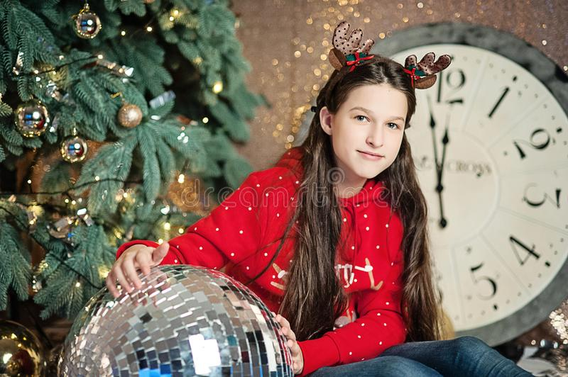Girl under christmas tree waiting for the new year near disco ball decoration. royalty free stock images