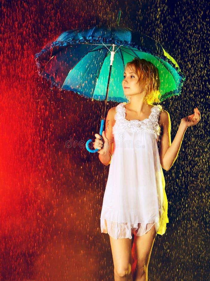 Girl Under Rain. Beautiful girl with umbrella under rain, black background stock photo