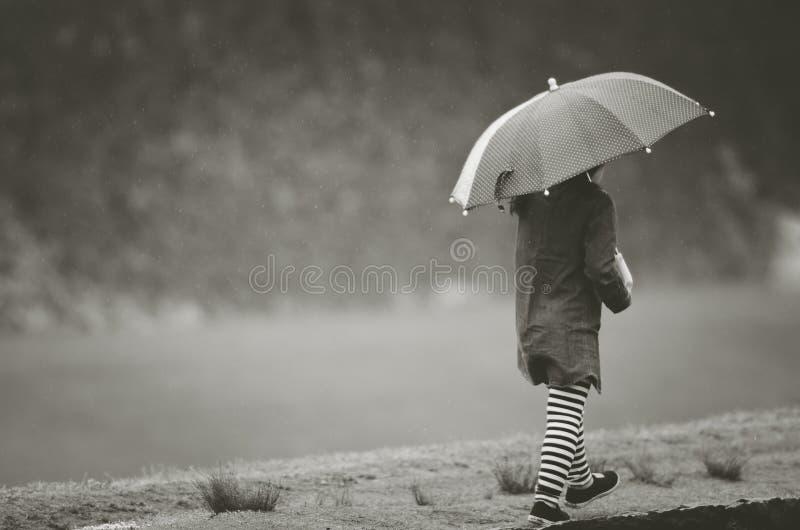 Girl under rain with umbrella. In black and white tone stock photos