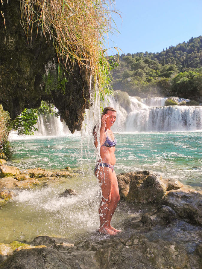 Girl under the waterfall. The girl under the thin streams waterfall stock photo