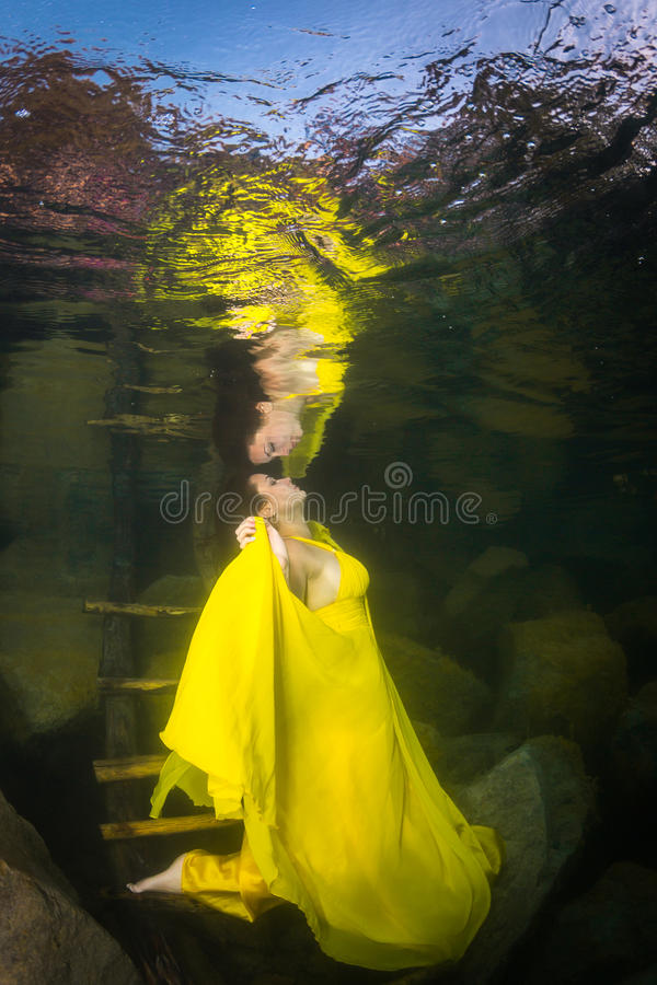 Girl underwater. Young graceful woman in a dress posing near the stairs in the lake stock image
