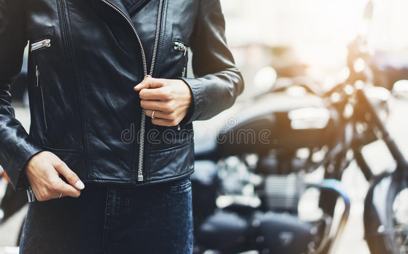 Girl unfastens black leather jacket on background motorcycle in sun flare atmospheric city, hipster biker female hands closeup. Motorbike street lifestyle royalty free stock photography