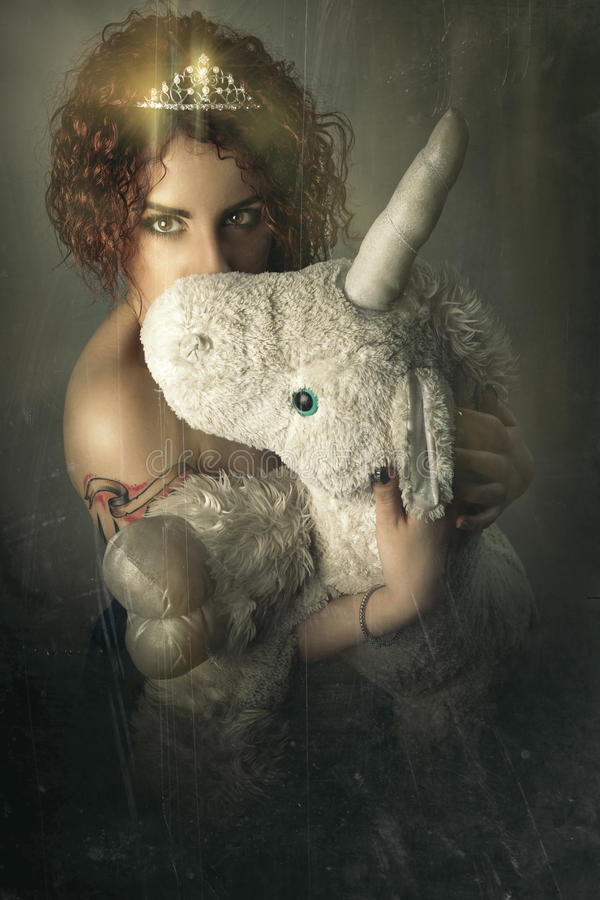 Girl with unicorn. Young woman hugging a unicorn puppet. stock photo