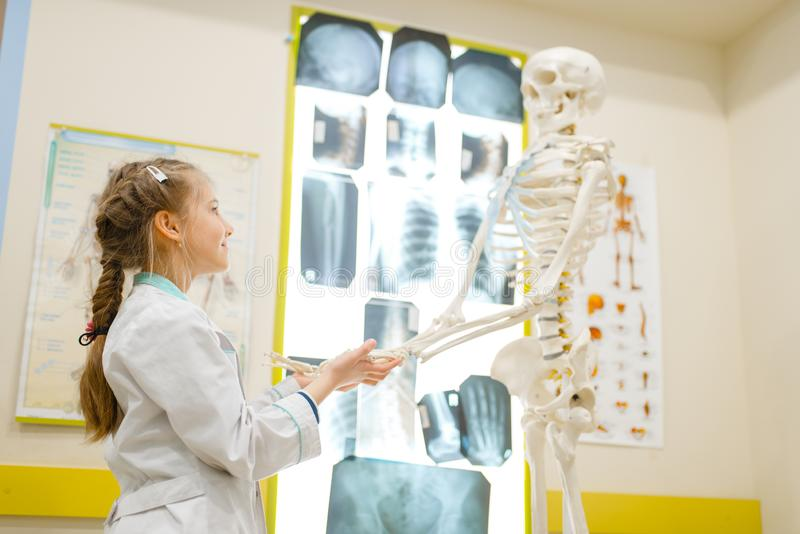 Girl in uniform playing doctor with human skeleton royalty free stock image