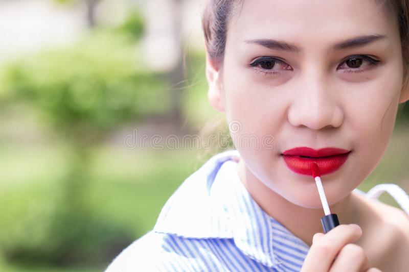 Girl use lipstick at the mouth. Fashion set sweet girl, Asian woman use lipstick. royalty free stock photo
