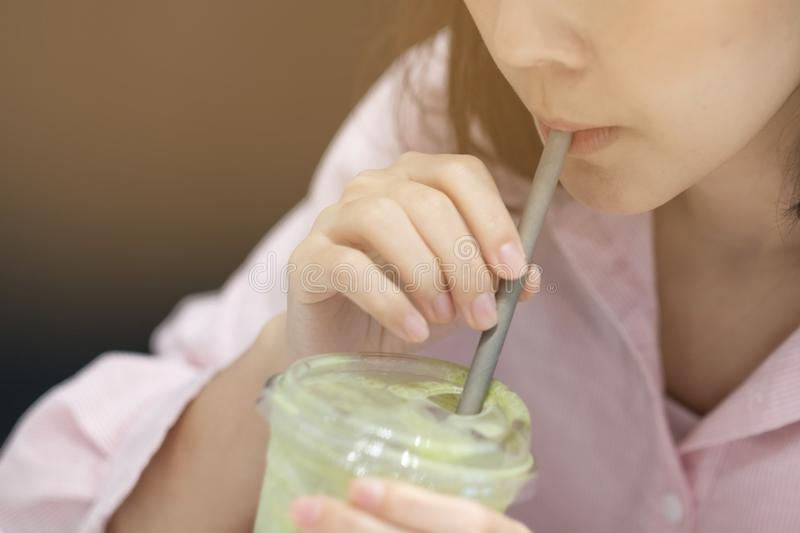 The girl used a Paper straw for drinking some water in coffee shop royalty free stock images