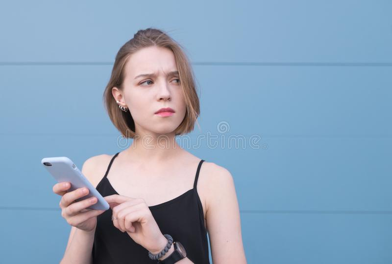 girl uses a smartphone on the background of a blue wall and looks out of sight with an interested look royalty free stock image