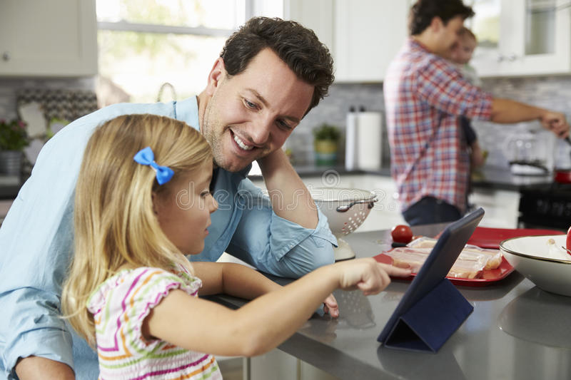 Girl uses tablet in kitchen with dad, while other dad cooks royalty free stock images