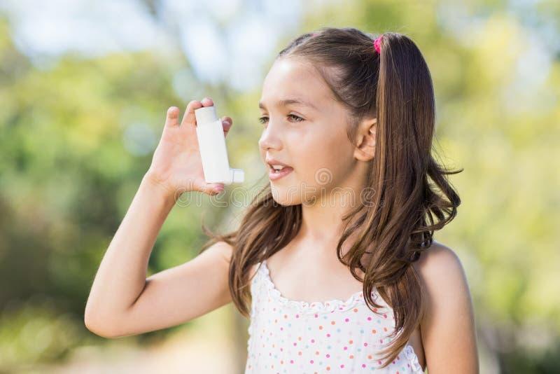 Girl using an asthma inhaler royalty free stock photo