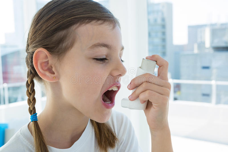 Girl using asthma pump royalty free stock photo