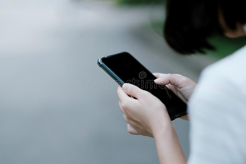 A girl using black smartphone for online shopping stock photo