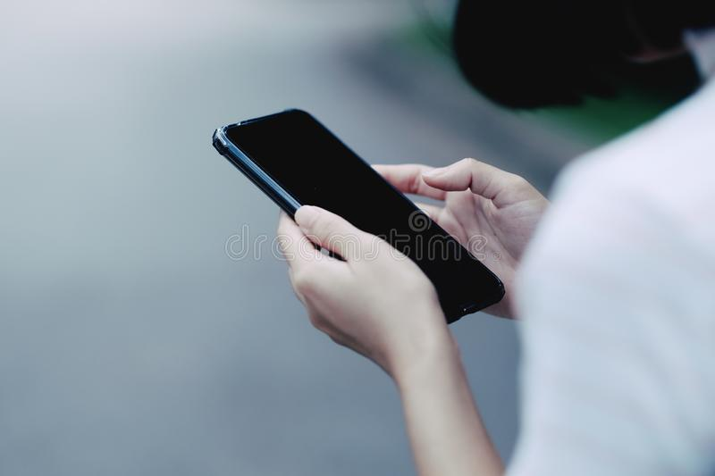A girl using black smartphone for online shopping stock photography