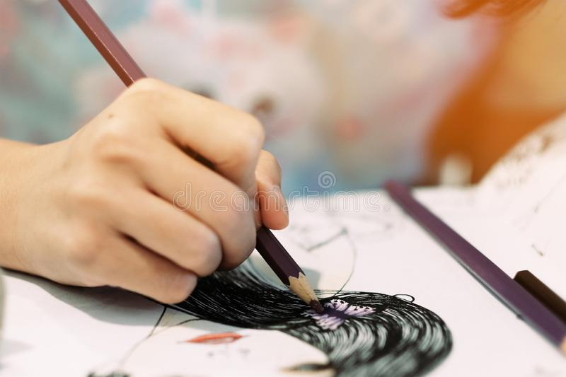 Girl using colored pencils to paint images royalty free stock images